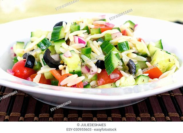 Mediterranean greek orzo pasta salad with black olive, red onion and cucumber