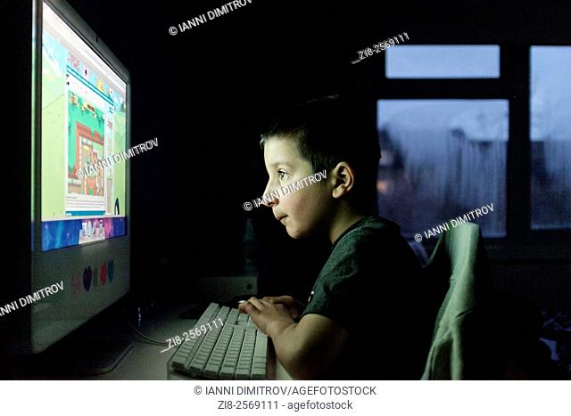 Boy ,7 years old, playing computer games at home