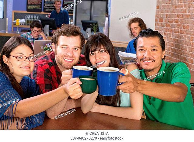 Four joyful people holding up coffee mugs