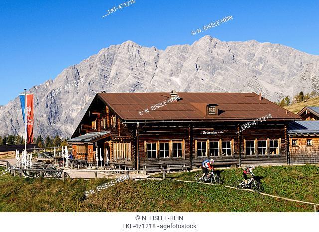 Mountain bikers passing Gotzenalm, mount Feuerpalven, Berchtesgadener Land, Upper Bavaria, Germany
