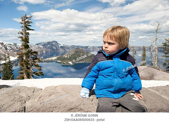 Little boy sitting at Crater Lake National Park in Oregon, USA