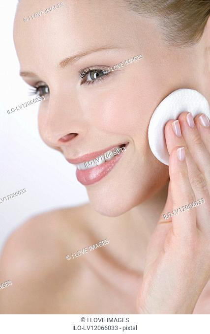 A portrait of a young woman cleansing her face, smiling