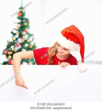girl in santa helper hat with blank white board