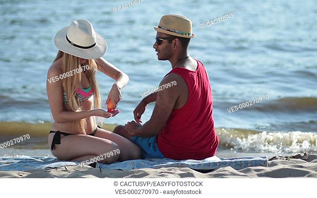 pretty woman applying sunscreen on man's shoulder