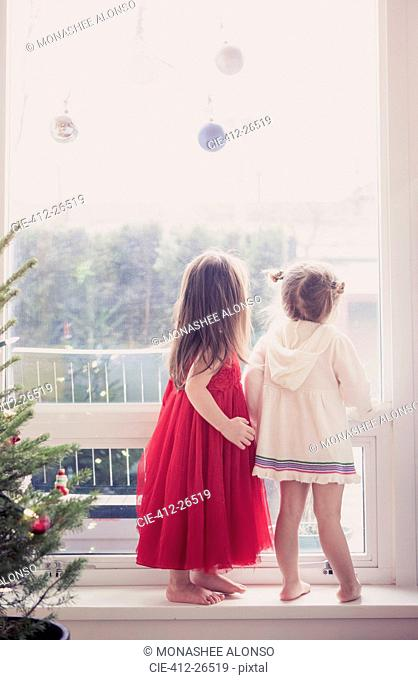 Girls on window ledge below Christmas ornaments