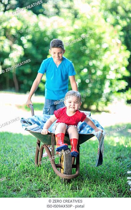 Young boy pushing sister in wheelbarrow