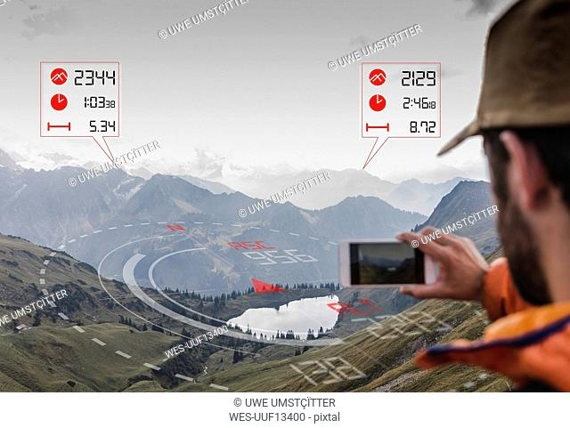 Young man on a hiking trip with data emerging from smartphone