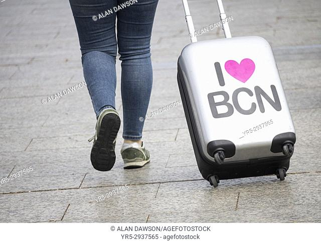 Tourist with i love Barcelona sticker on wheeled suitcase