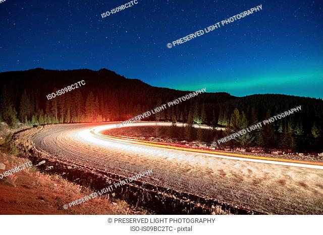 Northern lights, and long exposure light trails from vehicles on road, Nickel Plate Provincial Park, Penticton, British Columbia, Canada