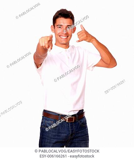 Handsome man in a studio, is smiling and pointing at you with a calling sign, on a white background