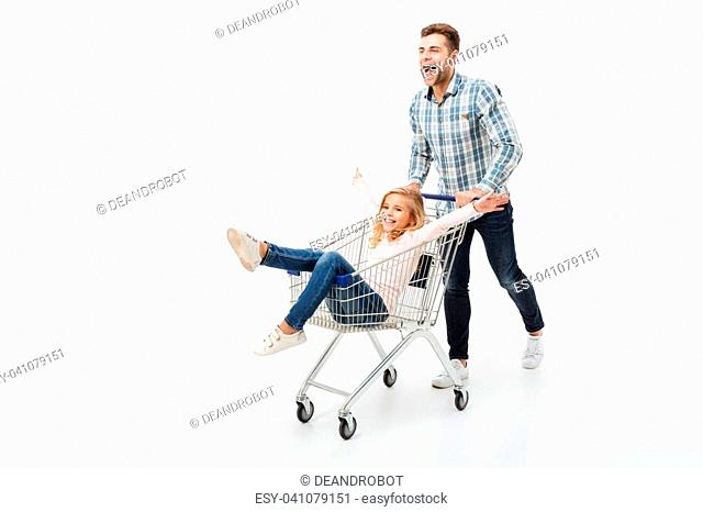 Full length portrait of a happy father giving a ride to his daughter on a shopping trolley isolated over white background