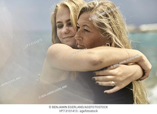 Mother (43 years) and teenage daughter (13 years) at seaside, bonding, embracing, enjoying togetherness. Danish ethnicity