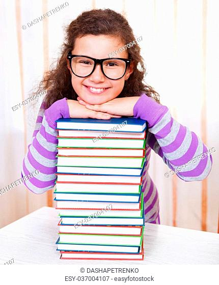Little brunette smiling girl with pile of books