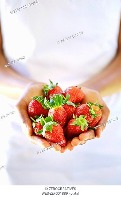 Woman's hands holding strawberries