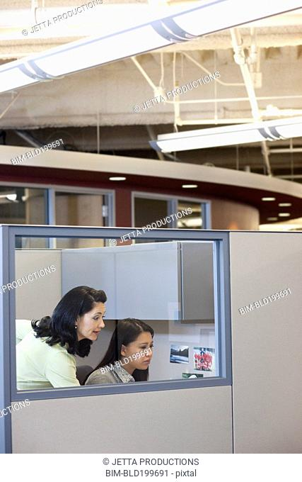 Businesswomen working together in office cubicle