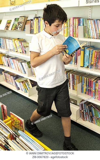UK,Surrey,UK- 10 years schoolboy choosing books in public library