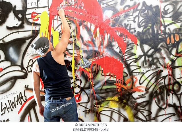 Man tagging wall with graffiti