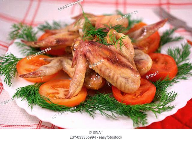 Grilled chicken wings with vegetables on the table