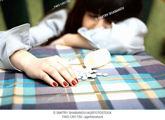 depression - women and drags open pack of pills on the table
