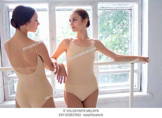 The two classic ballet dancers posing at ballet barre on a white room background