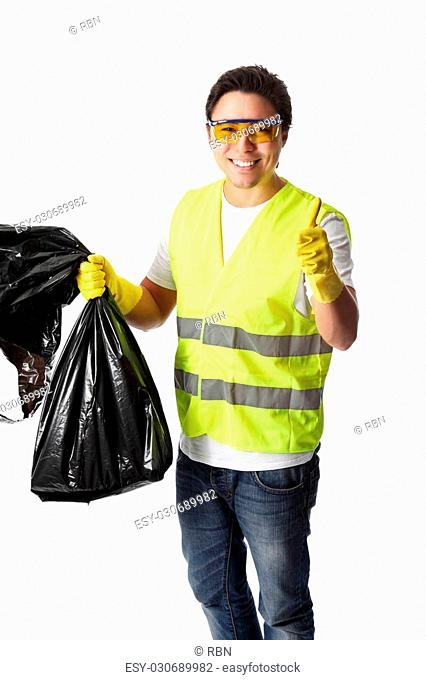 Young man standing wearing a reflective vest, gloves and safety glasses. Holding a black garbage bag doing thumbs up. White background