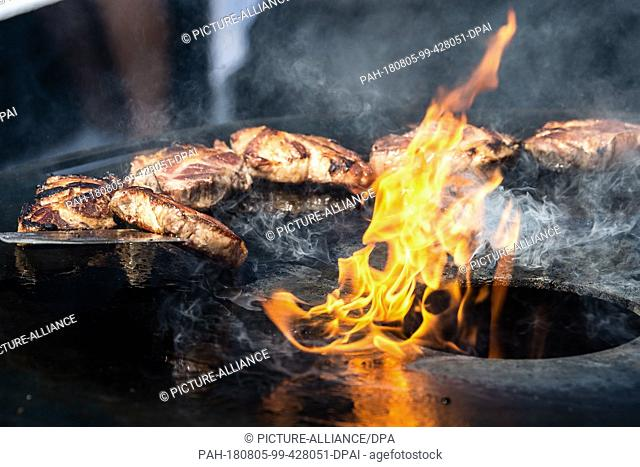05 August 2018, Germany, Fulda: A participant grills the neck of the Iberico pig on a fire grill. Over 35 competition teams compete in two classes for the title...
