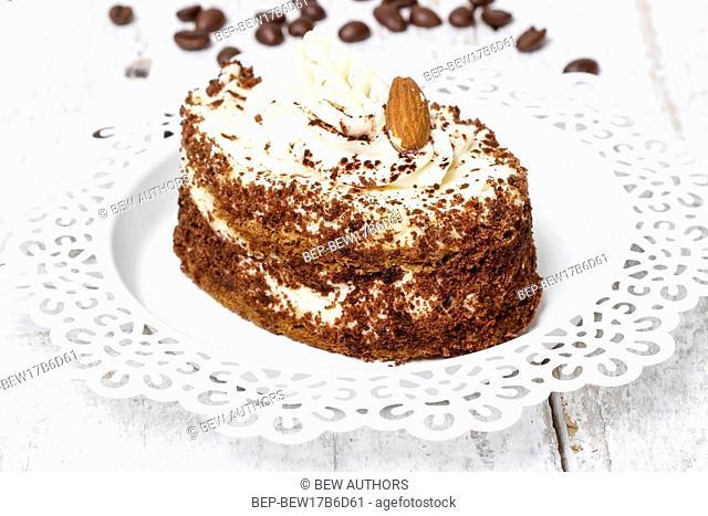 Tiramisu cake on white plate. Wooden background, selective focus