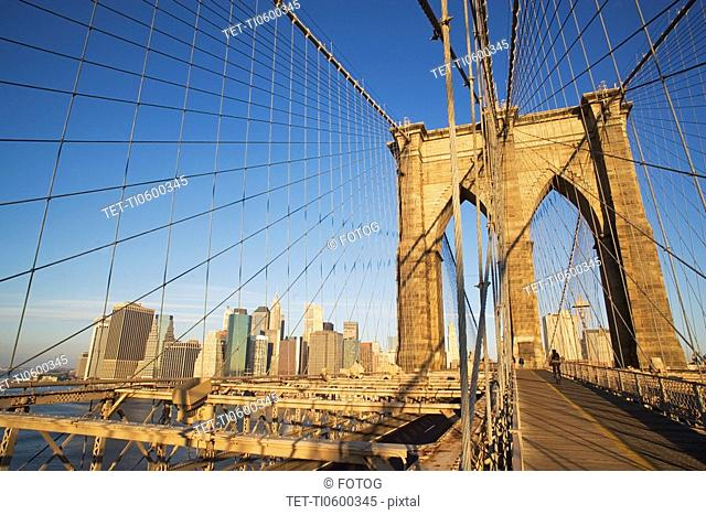 View of skyline through Brooklyn Bridge, New York City