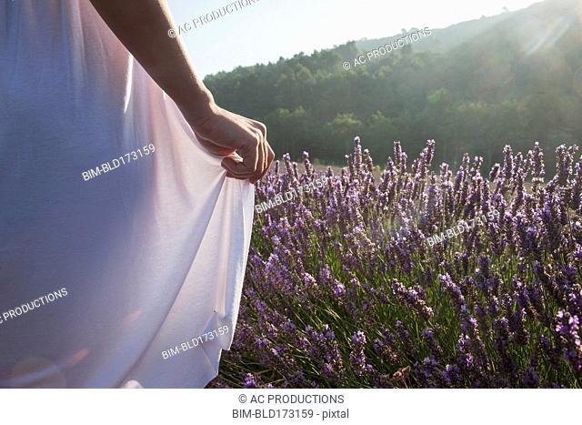 Caucasian woman walking in field of flowers