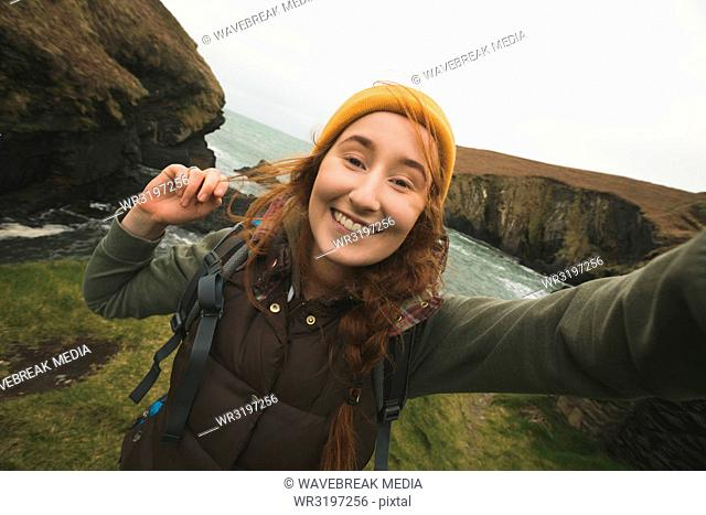 Smiling female hiker having fun near the sea