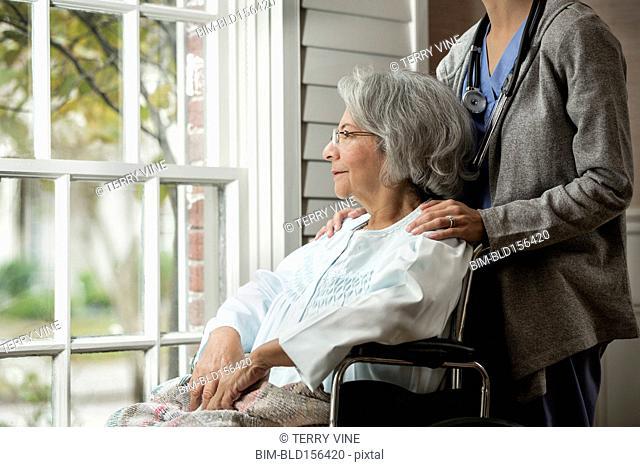 Nurse standing with patient in wheelchair near window