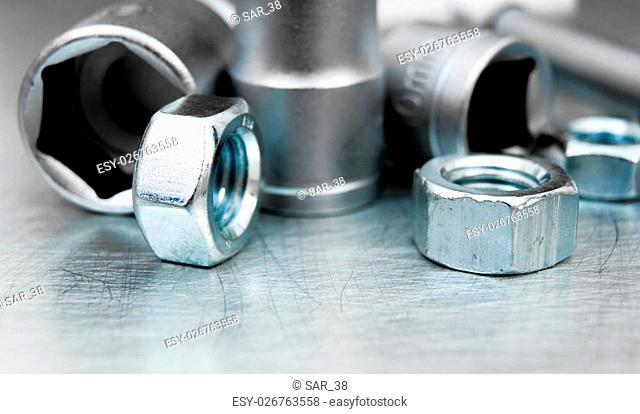Wrench heads and nuts on the scratched metal background