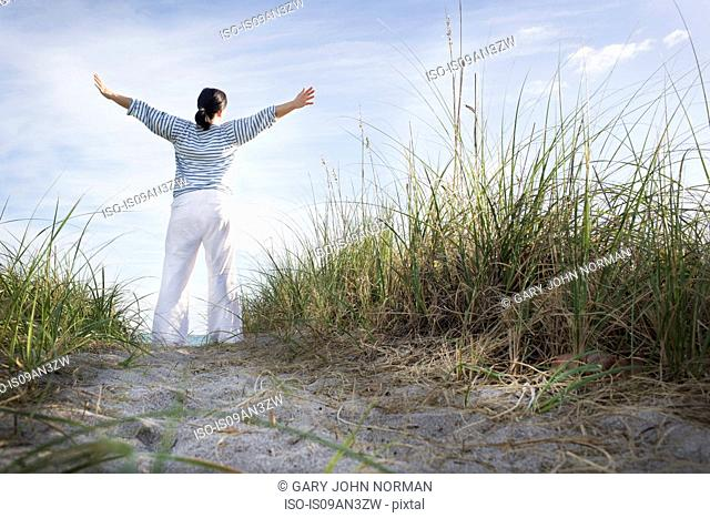 Mature woman with arms open on top of dunes, Juno Beach, Florida, USA