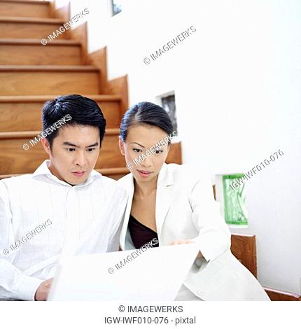 Businessman and businesswoman sitting on a staircase and looking at a laptop