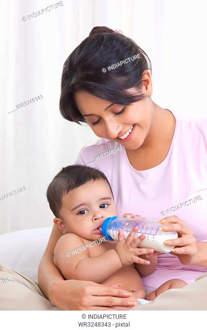 Mother feeding baby with milk from bottle