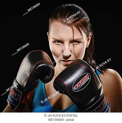 Boxing, young woman wearing a sportswear and she exercise, studio shot, black background