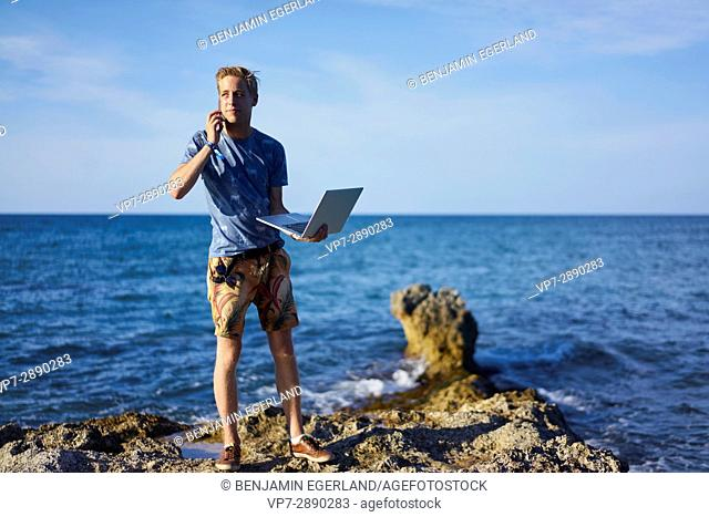 young man using mobile phone and laptop computer next to sea in holiday location Hersonissos, Crete, Greece