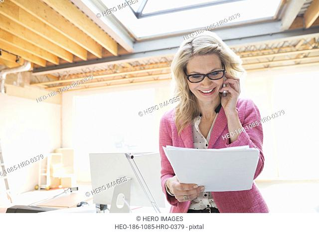Businesswoman reviewing paperwork in new office