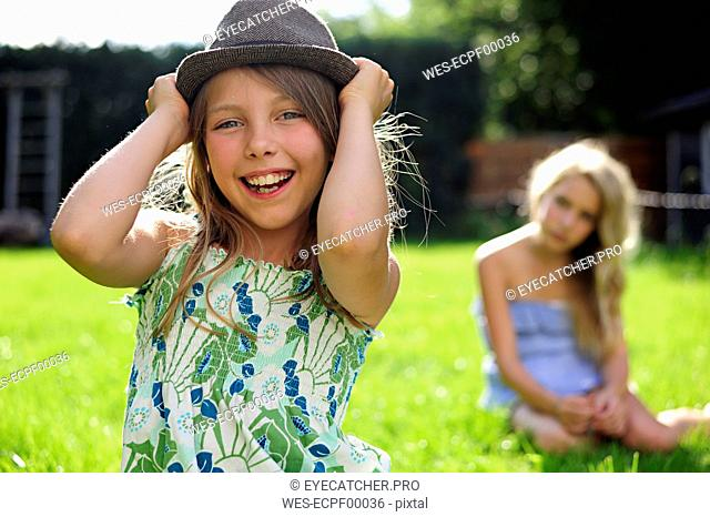 Happy playful girl putting on a hat in garden