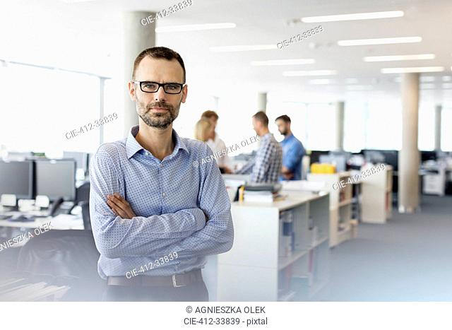 Portrait serious businessman with arms crossed in office