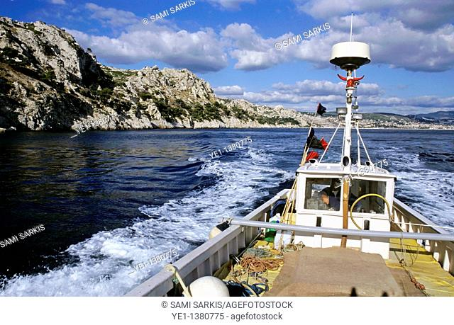 Fisherman steering a boat in the sea with coastline visible in the background