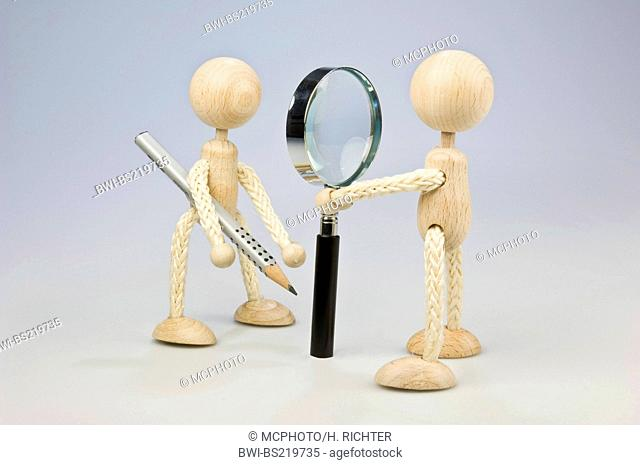 two wooden figures standing vis-a-vis, on with magnifier, one with pencil