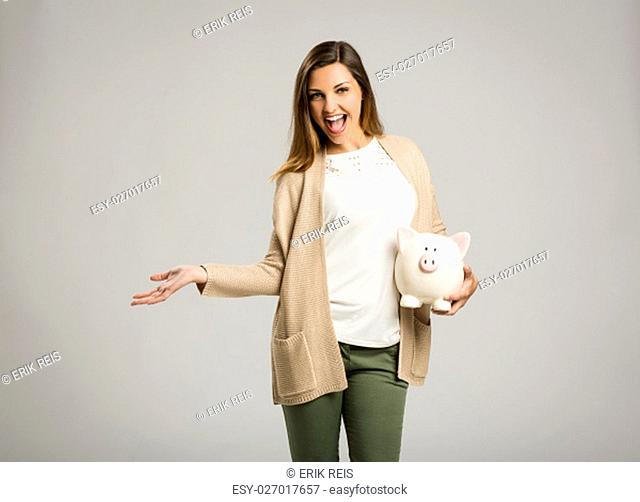 Beautiful and happy woman holding a piggy bank and making thumb up