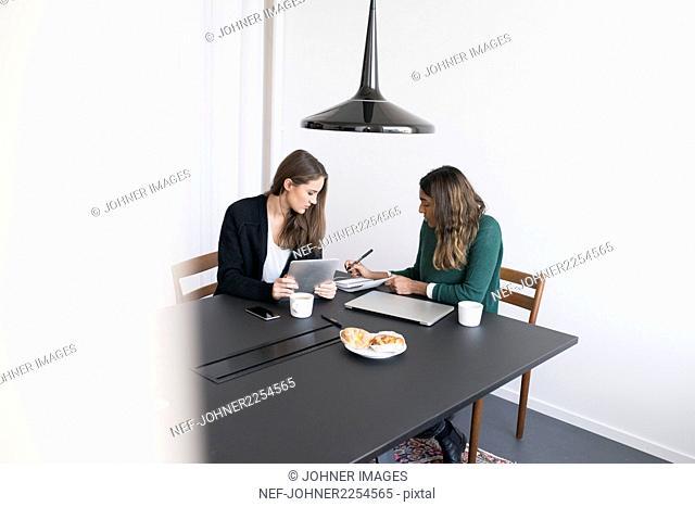 Two women using laptop in office