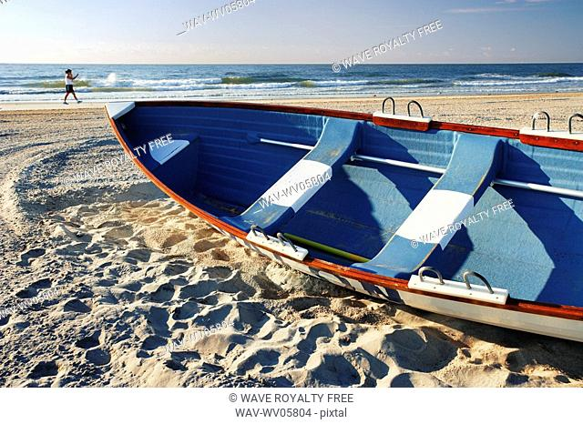 Woman walking on beach and small boat, New Jersy, USA