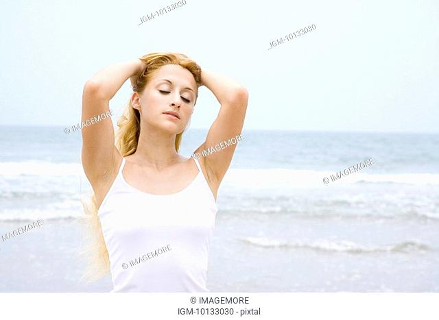 Young woman on beach with hands in hair