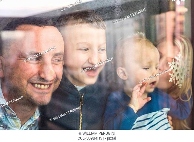 Mother, father and sons looking out of window, squashing faces against glass