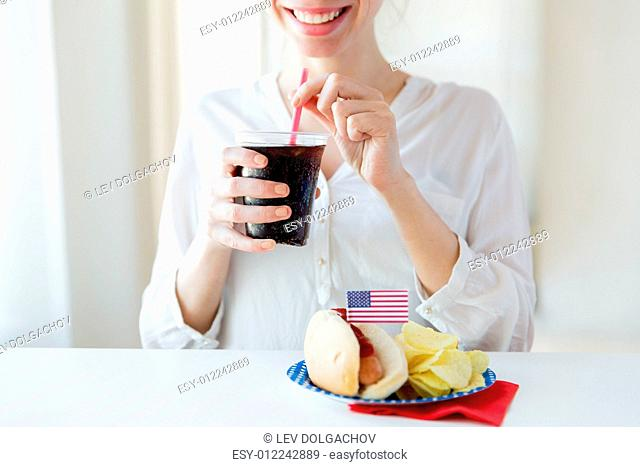 american independence day, celebration, patriotism and holidays concept - close up of happy woman drinking coca cola from plastic cup with hot dog and potato...