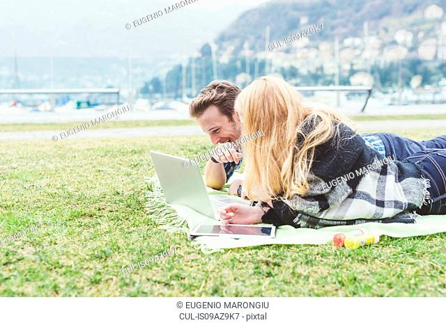 Young couple lying on picnic blanket looking at laptop, Lake Como, Italy