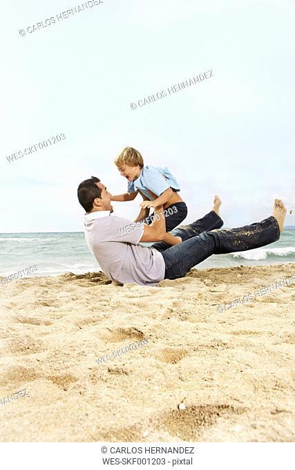 Spain, Father and son having fun on beach at Palma de Mallorca, smiling